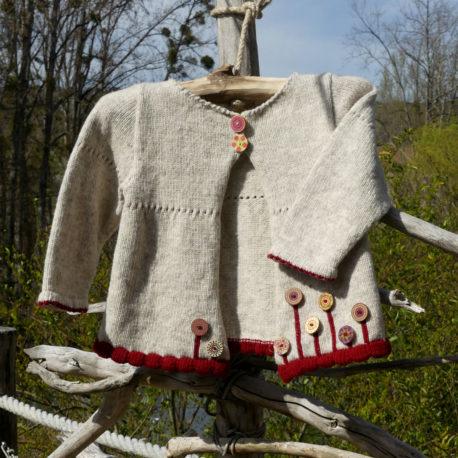 Cardigan Zelda d'une jolie couleur écru et une bordure couleur rouge dragon, boutons en bois qui représentent des fleurs au bas du pull