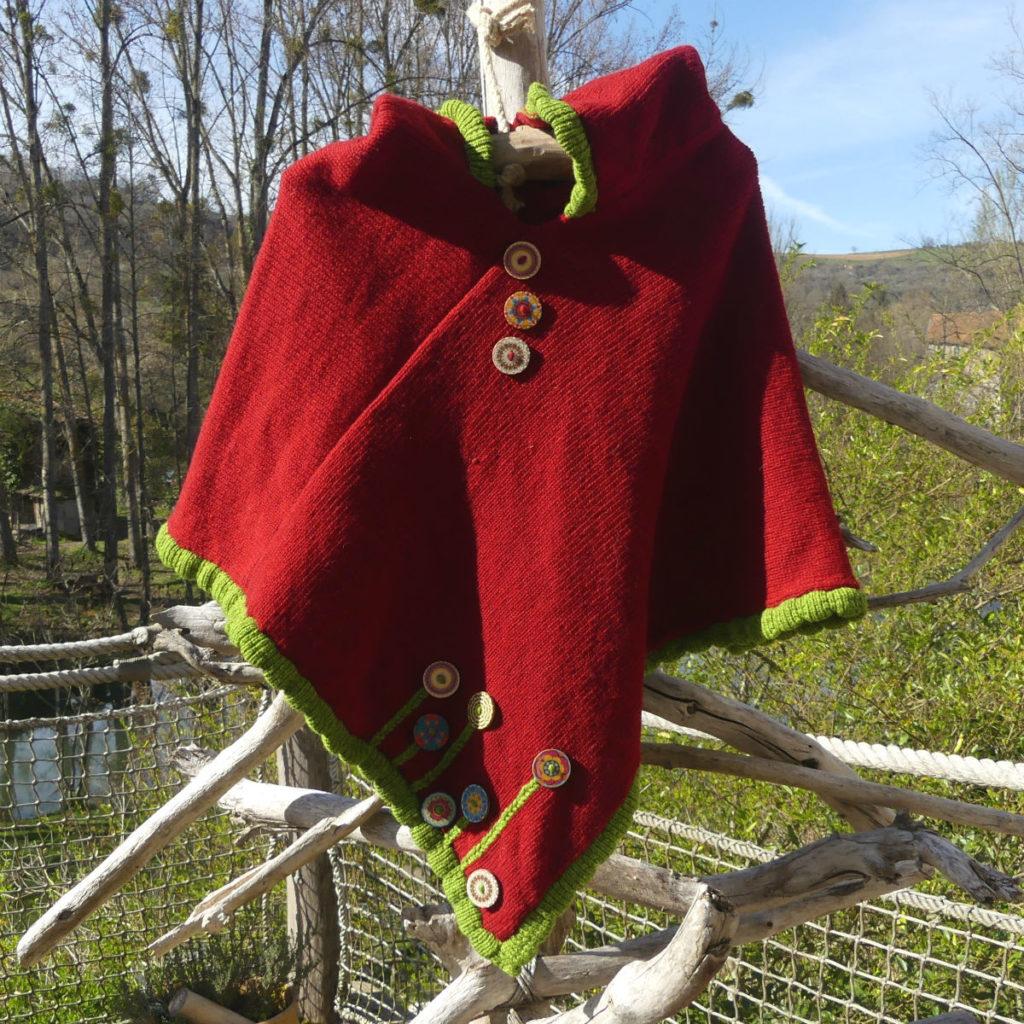 Poncho Coquelicot à capuche , couleur écru lègèrement chiné avec une bordure rouge pour les finitions. Au bas du poncho il y a des boutons en bois que donne une impréssion de fleurs.