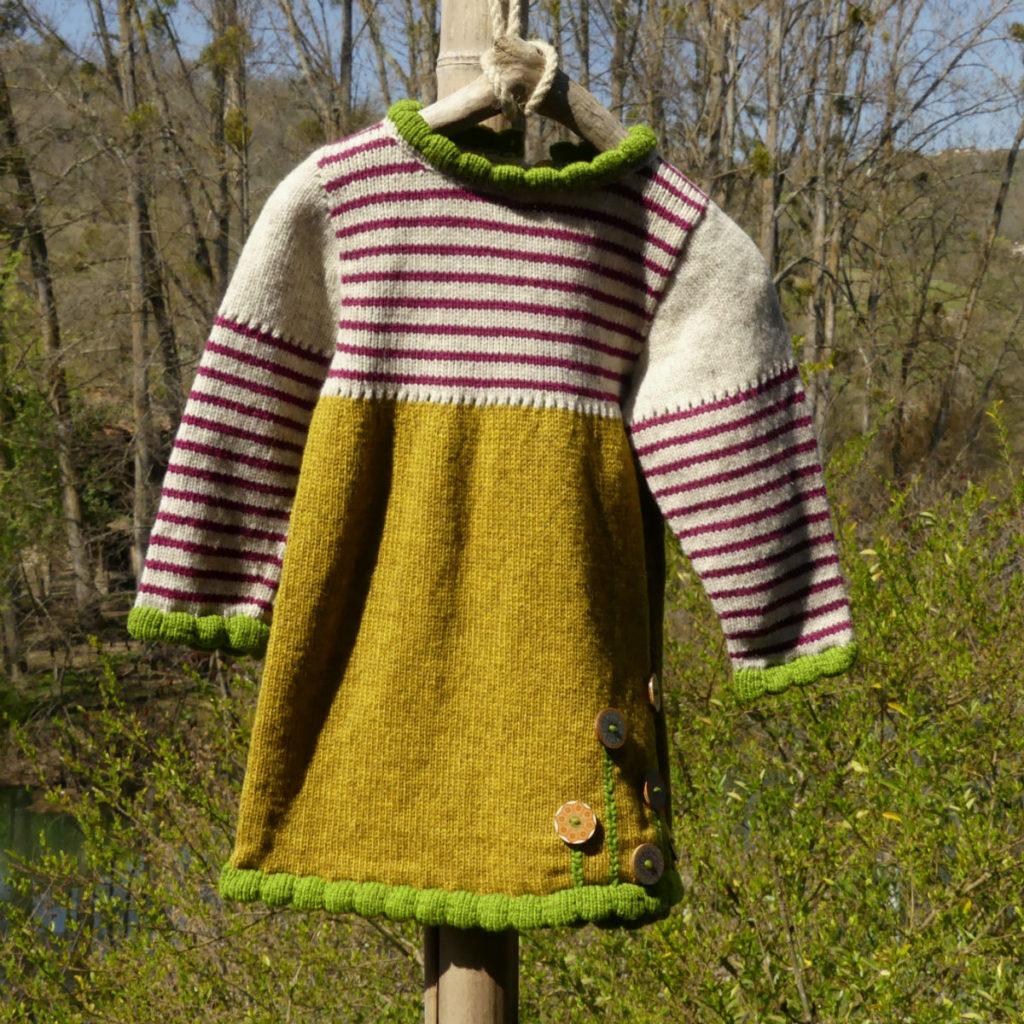 Robe en laine couleur ocre avec des bordures couleurs vertes et le haut est rayé couleur framboise sur un fond écru