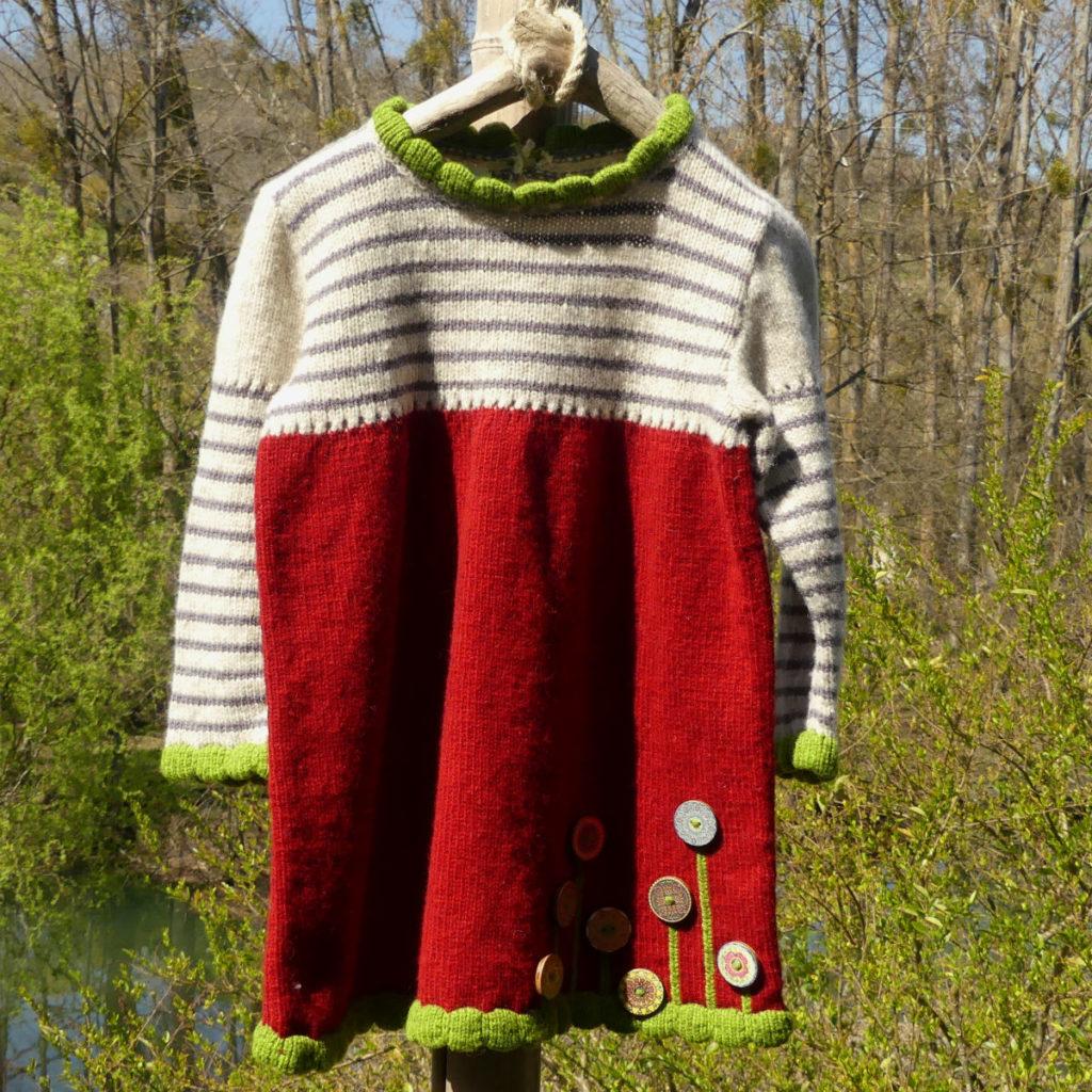 Robe en laine Coquelicot , d'une couleur rouge avec des bordures vertes aux manches, col et bas de la robe.Des boutons en bois ornent le bas