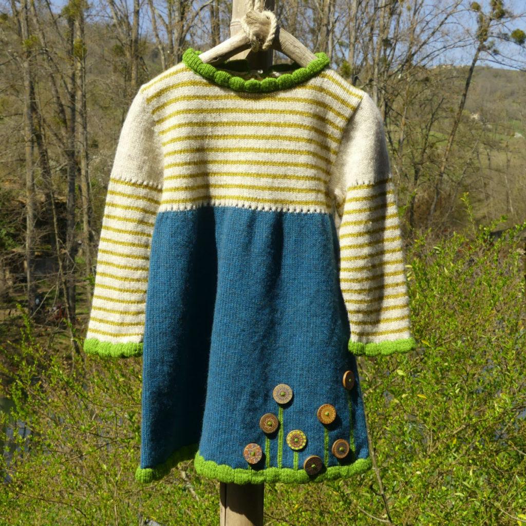 Robe en laine couleur bleu canard avec le haut écru et rayé couleur ocre. des bordures vertes pour les finitions.