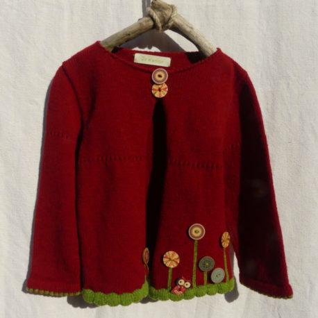Cardigan manche longue de couleur rouge foncé avec une bordure pour les finitions de couleur verte . des boutons bois motif fleur au bas du cardigan.