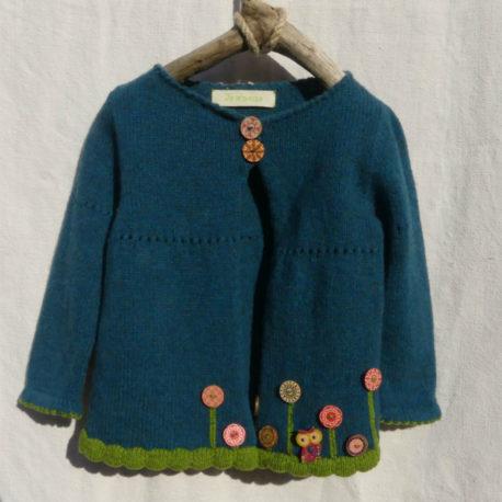 Cardigan fillette couleur bleu canard et du vert pour les bordures de finitions. des boutons en bois motif fleur au bas du cardigan