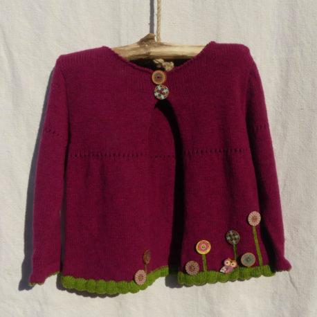 Cardigan d'une couleur framboise avec du vert pour les finitions des bordures. des boutons motifs fleurs au bas du cardigan.
